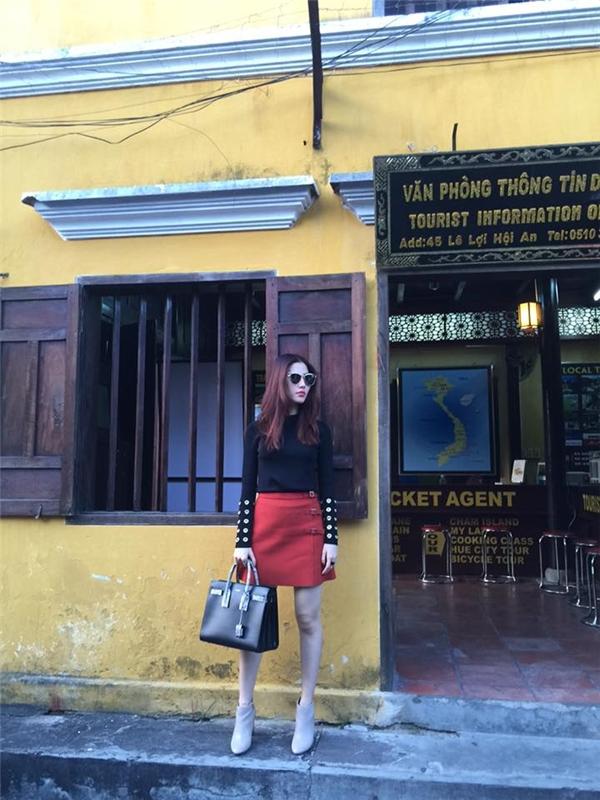 Hình ảnh cô gái thanh lịch, hiện đại được Diễm My 9x khắc họa rõ nét trên đường phố Hội An với áo phông tay dài, chân váy midi tông đỏ nổi bật.