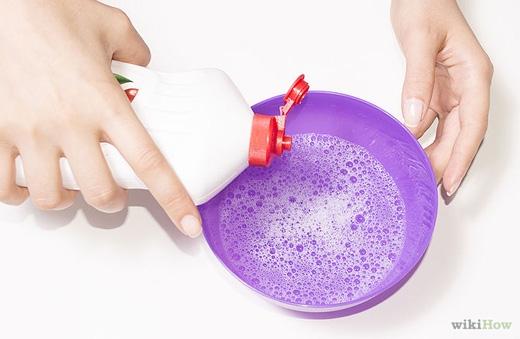 Pha thuốc tẩy quần áo dạng lỏng vào nước nóng rồi ngâm tay vào đó và chà nhẹ khoảng 20 phút. (Ảnh: Internet)