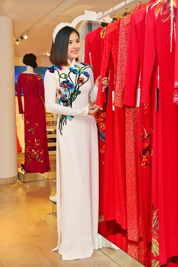 Thiết kế áo dài trắng thanh tao được tạo điểm nhấn bằng những họa tiết hoa thêu tay với tông màu trầm tương phản.
