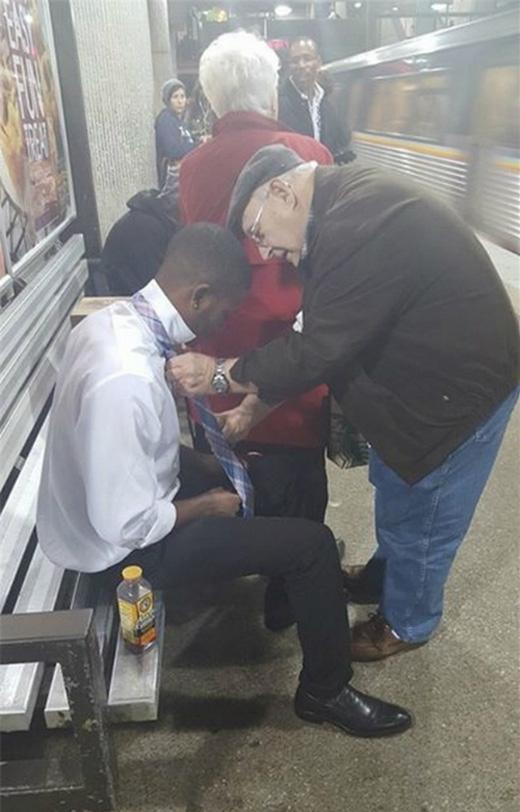 Một cụ già hướng dẫn cho một thanh niên lạ mặt tại ga điện ngầm cách thắt cà vạt. (Ảnh: Internet)