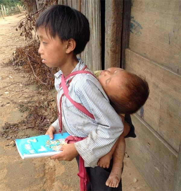 Khoảnh khắc cậu bé mặt mũi lấm lem bùn đất, lưng địu em nhỏ và cầm quyển sách trên tay để học bài khiến cộng đồng mạng rơi nước mắt. (Ảnh: Internet)