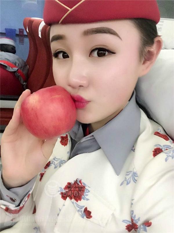 Nữ tiếp viên hôn lên quả táo.(Ảnh: Internet)