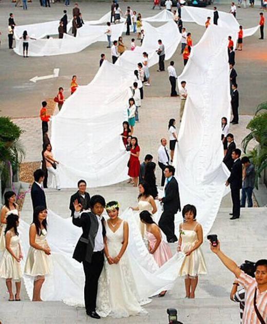 Cặp đôi đang sinh sống tại Quảng Châu, Quảng Đông, Trung Quốc đã gây ấn tượng mạnh với quan khách bằng chiếc váy dài hơn 200m và nặng gần 100kg. Được biết, cô dâucó tên là Xie Qiyun. (Ảnh: Internet)