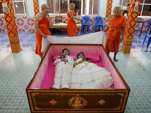 """Chú rể 40 tuổi TanapatpurinSamangnitit và cô dâu 26 tuổi Sunantaluk Kongkoon tại Thái Lan là một trong 7 cặp đôi được """"trải nghiệm cái chết"""" ngay trong lễ cưới của mình bằng việc nằm vào quan tài. Theo quan niệm của người dân nơi đây, nằm trong đó sẽ giúp các cặp vợ chồng loại bỏ những điều xui xẻo trước khi đến với nhau. (Ảnh: Internet)"""