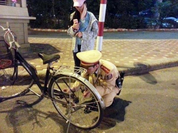 Một chiến sĩ CSGTsửa xe đạp giúp người đi đường. Ảnh: Internet