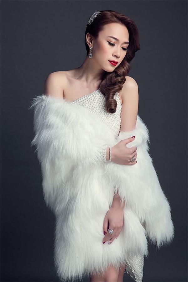 Mỹ Tâm mang đến tạo hình gợi cảm, nhẹ nhàng trong cả cây trắng kết hợp váy lệch vai cùng áo choàng lông bên ngoài. Trong năm 2015 vừa qua, gu thời trang của nữ ca sĩ đã nhanh chóng thay đổi theo hướng tích cực hơn.