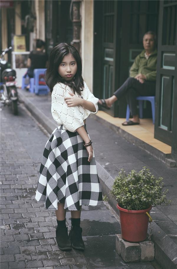 """Ju Uyên Nhi điệu đà khi chọn phối giữa áo phông phom rộng cùng chân váy xòe kẻ caro to bản. Chất liệu nỉ, len dạ tái hiện rõ nét âm hưởng đặc trưng của mùa thời trang Thu - Đông. Ju Uyên Nhi cho biết: """"Con rất thích thời trang. Trong trường Hàn Quốc ngoài giờ học chúng con cũng được thầy cô chia sẻ về những kĩ năng thẩm mĩ như phối màu, chất liệu,vẽ và có tài liệu về thời trang dành cho trẻ em nữa. Giờ giải lao con thường lên thư viện tìm sách về thời trang trẻ em đọc. Con rất thích thú khi biết cách tự chọn trang phục cũng giúp mẹ em đỡ phải đau đầu."""""""