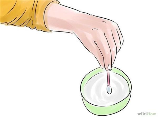 Thấm ướt tăm bông bằng dung dịch rửa. (Ảnh: Internet)
