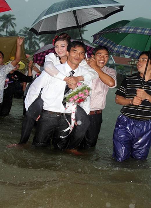 Cơn mưa nặng hạt trên đầu trong khi nước dâng ngập đến gối vẫn không làm chùn bướcchú rể, một lính hải quân tại Cam Ranh, Khánh Hòa. (Ảnh: Internet)