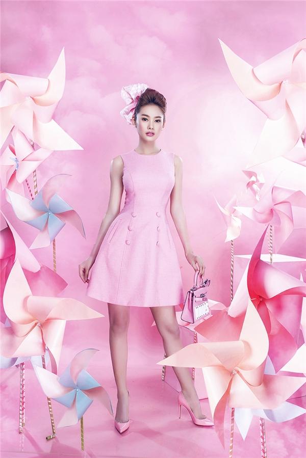 Linh Chi ngọt ngào, nhẹ nhàng khi diện dáng váy xòe cổ điển kín đáo, thanh lịch. Sắc hồng càng làm tôn lên nét yêu kiều, quyến rũ cho người đẹp 9x. Thiết kế được tạo điểm nhấn đơn giản bằng túi cắt xéo cùng những cúc áo to bản đối xứng hai bên.
