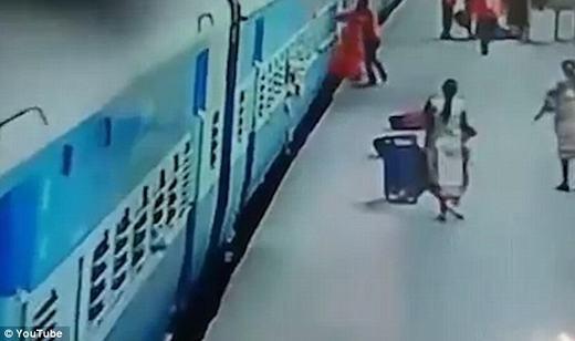 Người phụ nữ áo đỏ bước xuống, nhưng tà váy bị vướng vào tàu. (Ảnh: chụp màn hình)