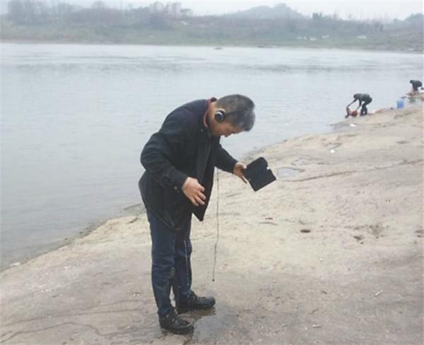 Người anh hùng áo đen còn mặc nguyên quần áo và đeo tai nghe sau khi cứu cháu bé từ dòng sông. (Ảnh: The Shanghaiist)
