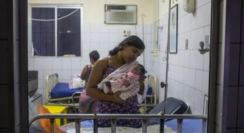 Một người mẹ ôm đứa con mắc chứng đầu nhỏ, do virus ăn não người gây ra. Ảnh: Internet