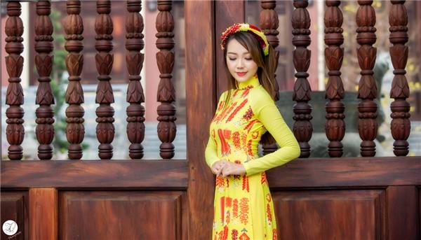 Băng Di mặc trang phục áo dài của NTK Tuấn Trần với hoa văn là những cây pháo đỏ ngày Tết cổ truyền, mang đến sự phá cách cho tà áo dài truyền thống. - Tin sao Viet - Tin tuc sao Viet - Scandal sao Viet - Tin tuc cua Sao - Tin cua Sao