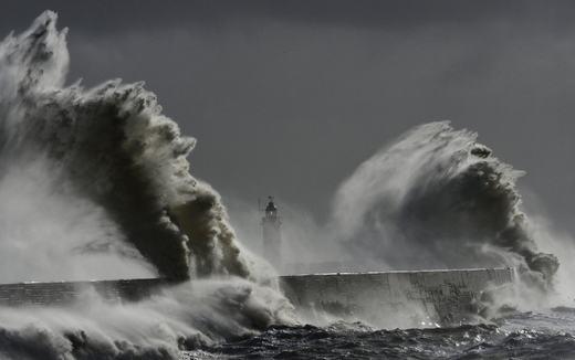 Sóng lớn đánh vào ngọn hải đăng và bến cảng khi thủy triều dâng cao tại Newhaven, Sussex, miền Nam nước Anh vào ngày 15/2/2014. (Ảnh: NOAA)