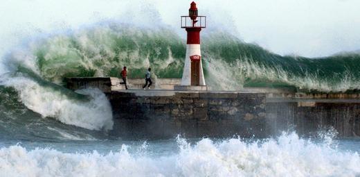 Sóng khổng lồ tấn công 2 người đàn ông tại bến cảng Kalk Bay Cape Town ở Nam Phi. Hai người này sau đó đã được cứu thoát. (Ảnh: NOAA)