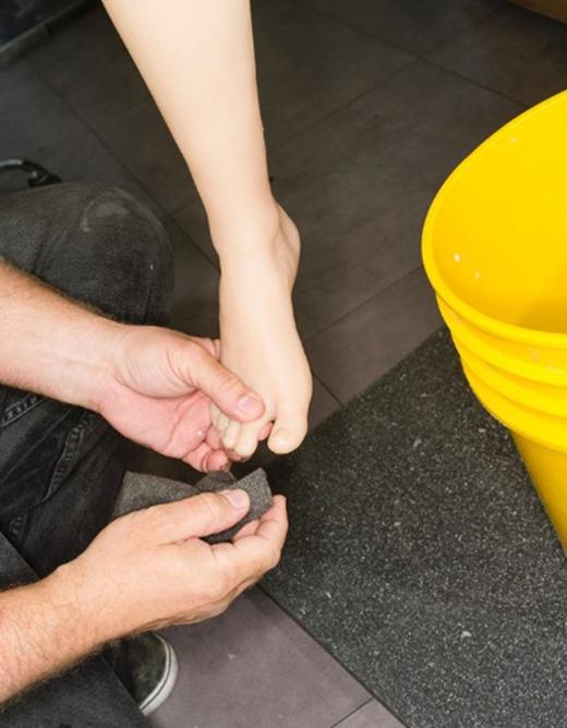 Phần móng chân búp bê được một nhân viên nhà máy hoàn thiện. (Ảnh:Robert Benson)