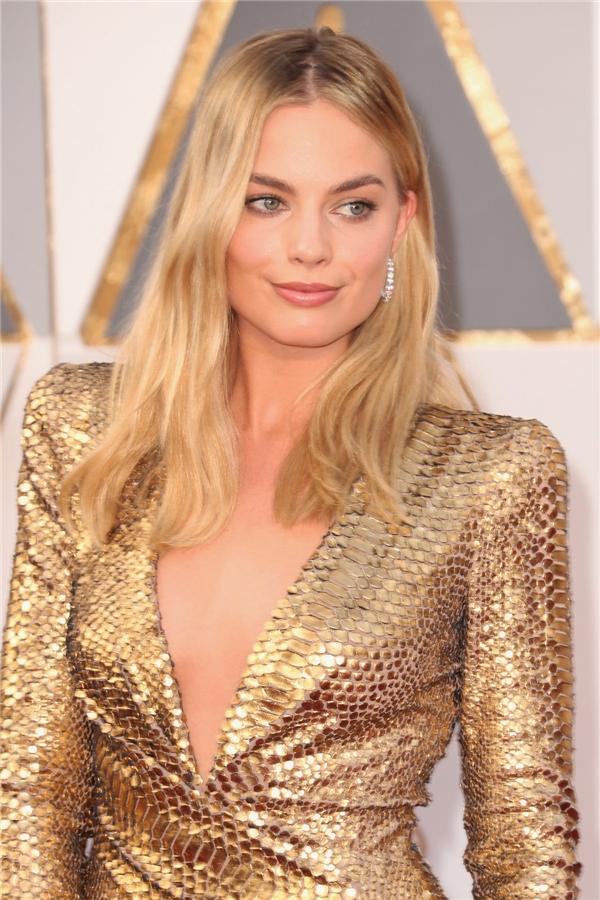 Margot Robbie diện bộ cánh có tông vàng ánh kim nổi bật. Kết hợp cùng thiết kế sang trọng này là gương mặt được trang điểm nhẹ nhàng, tự nhiên với điểm nhấn vào màu môi cam đất gần như đồng điệu với sắc da.