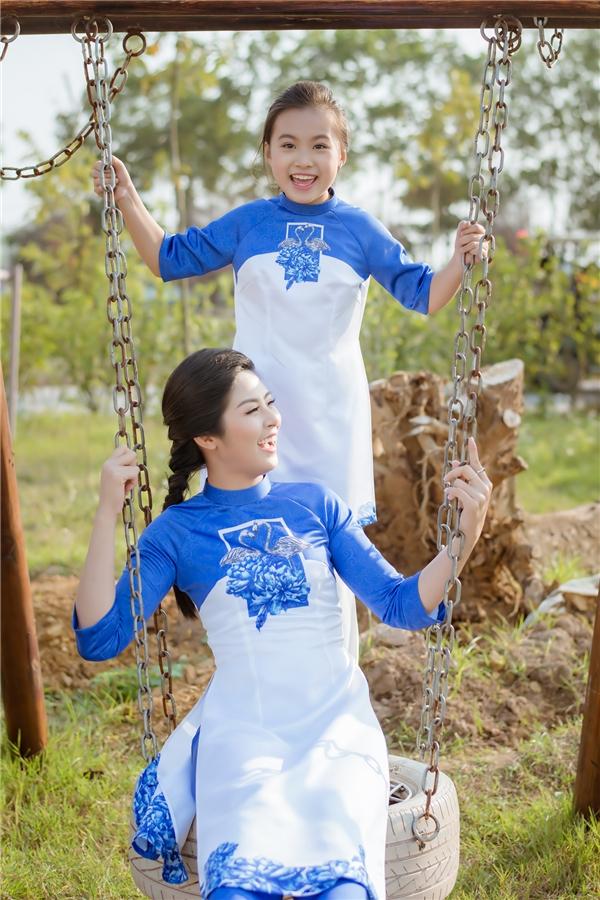 Hoa hậu Việt Nam 2010 và con gái nuôi diện áo dài cách tân với hai tông màu xanh, trắng làm chủ đạo. Thiết kế tạo điểm nhấn bởi những bông hoa phù dung to bản cùng cách phối các mảng màu vừa phân tách nhưng lại vừa hòa hợp.