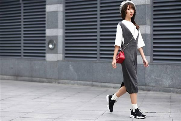 Quỳnh Anh Shyn kết hợp áo phông trắng đơn giản cùng quần yếm trẻ trung, điệu đà. Mũ bê-rê cùng giày thể thao đi kèm tạo nên sự tương phản thú vị với tổng thể. Cô nàng sử dụng chiếc túi với kích thước nhỏ nhưng chúng vẫn trở thành điểm nhấn nhờ sắc đỏ nổi bật không thể hòa lẫn vào đâu.