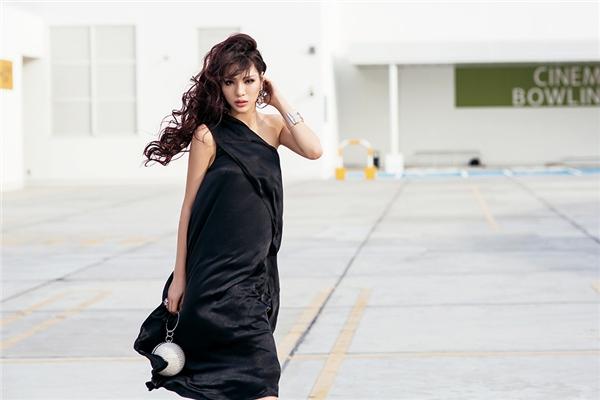 Giải vàng Siêu mẫu Việt Nam 2015 giấu đường cong trong dáng váy rộng, chéo vai. Thiết kế với chất liệu mềm mại càng làm tăng thêm vẻ nữ tính, quyến rũ cho cô nàng.