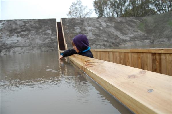 Một em bé đang nghịch nước trên cầu. (Ảnh: Internet)
