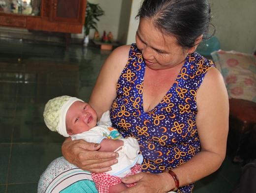 Cháu bé bị bỏ rơi trong vòng tay bà Lê Thị Tâm. (Ảnh: Internet)