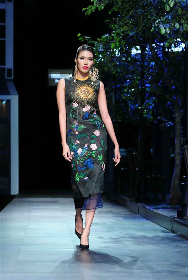 Lan Khuê diện bộ váy trên nền sắc xanh, đen thẫm kết hợp những hoạ tiết thêu tay, đính kết kì công, tỉ mỉ. Tất cả như tái hiện bức tranh hoa lá mùa Xuân - Hè của vùng nhiệt đới. Những sải chân đều đặn cùng cách đánh hông uyển chuyển, Top 11 Hoa hậu Thế giới 2015 như thổi hồn vào bộ trang phục giúp chúng trở nên lung linh, lộng lẫy hơn.