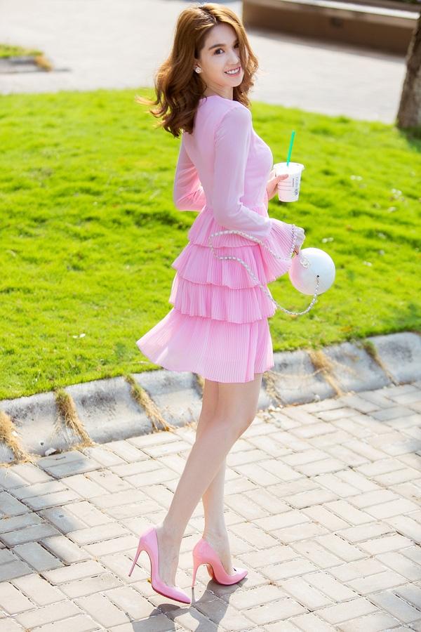 Sải bước trên phố trong những ngày đầu hè, Ngọc Trinh làm dịu bớt cái nắng gắt với vẻ ngoài ngọt ngào, thanh thoát. Nữ người mẫu diện bộ váy hồng trên nền voan lụa mềm mại. Thiết kế kín cổng cao tường tạo điểm nhấn bởi những đường xếp li cùng cấu trúc phân tầng độc đáo.