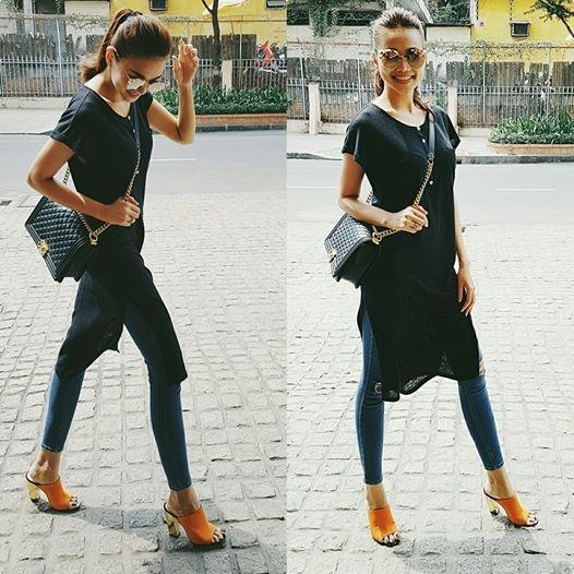 Thanh Hằng khéo léo kết hợp quần jeans skinny cùng áo phom rộng, dáng dài xẻ tà với hai tông màu: xanh, đen cơ bản. Nhìn sơ lược tổng thể, chắc chắn đôi giày cao đế thô sẽ là điểm nhấn nổi bật nhất với sắc vàng cam ngọt ngào, nóng bỏng.