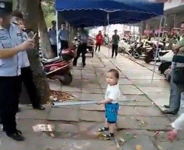 Cậu bé 3 tuổi tay cầm gậy sắt bảo vệ bà trước cán bộ địa phương.