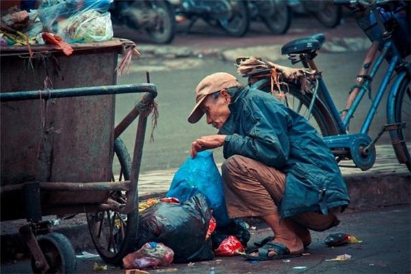 Cụ ông loay hoay nhặt đồ thừa tại thùng rác, nhất quyết không xin tiền từ mọi người. Ảnh: Sơn Tùng.