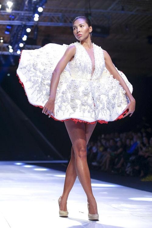 Thoạt nhìn, chiếc váy này khá đơn giản và nhẹ nhàng để di chuyển. Nhưng số lượng lớn ngọc trai đính kết trên toàn bộ thân váy đã nâng khối lượng lên hơn 20 kg và trở thành một thử thách với Minh Triệu trên sàn catwalk. Thiết kế này nằm trong bộ sưu tập Hoa của Lê Thành Hòa từng được trình làng vào năm 2014.