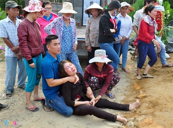 Bà Phạm Thị Phương trong giây phút người dân đưa quan tài con trai xuống huyệt chôn cất.