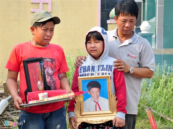 Người thân cầm di ảnh nạn nhânPhạm Xu Sum, họ khóc nức nở khi quan tài của em hạ huyệt.