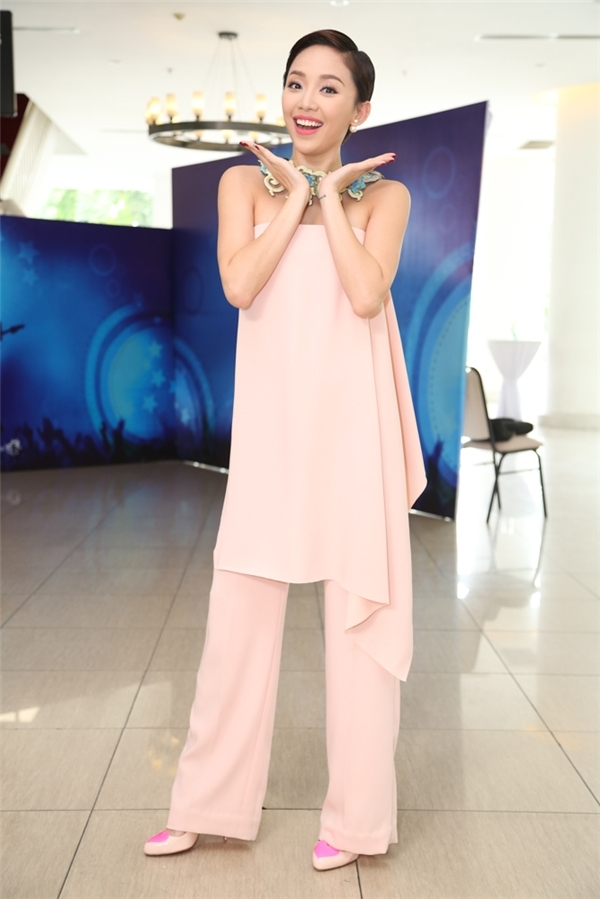 Trên ghế nóng Vietnam Idol Kid 2016, Tóc Tiên cũng chọn diện trang phục với sắc hồng hợp xu hướng. Tuy nhiên, nữ ca sĩ lại gây bất ngờ khi giấu đường cong trong phom váy rộng bất đối xứng kết hợp cùng quần âu. Tổng thể trở nên thú vị hơn khi được Tóc Tiên kết hợp cùng vòng cổ to bản lạ mắt.