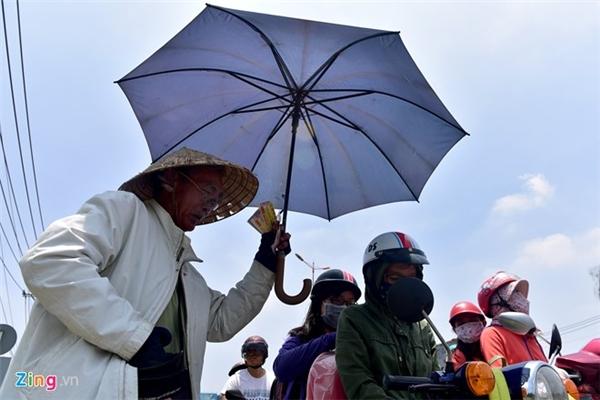 """""""Đội nón, mặc áo khoác, đeo găng tay như thế này nhưng cái nắng gắt vẫn xuyên qua. Tôi phải dùng thêm chiếc ô che nắng mới có thể trụ được để bán giữa đường"""", cụ Tám (82 tuổi) làm nghề bán vé số tại ngã tư Bình Thái, quận 9 chia sẻ."""