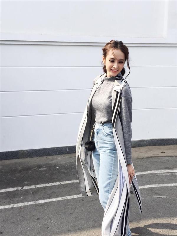 Chiếc quần jeans màu nhạt bên trên tiếp tục được Phương Trinh biến tấu cùng áo phông cổ lọ bên trong và áo khoác kẻ sọc bất đối xứng bên ngoài.