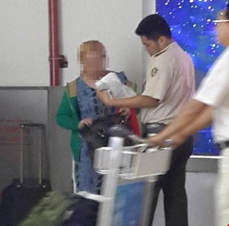 An ninh sân bay làm việc với mẹ của cháu bé. (Ảnh do nhân chứng cung cấp)
