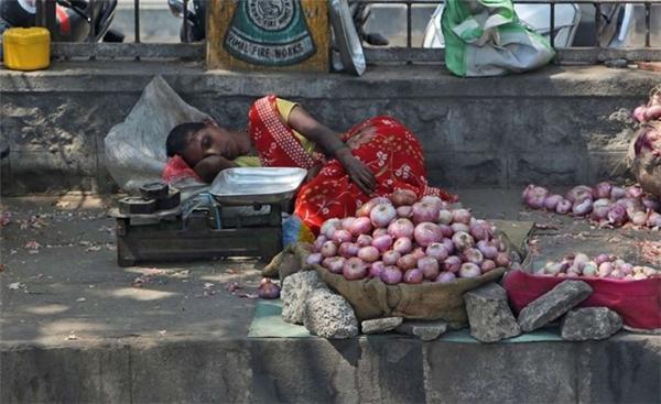 Một người bán hàng ngủ gật ven đường ở Kolkata.Washington Postcho biết, hàng chục nghìn súc vật của các hộ nông dân đã chết do trời nóng, mùa màng bị hư hại, các hồ, sông nhỏ đều cạn kiệt nước.