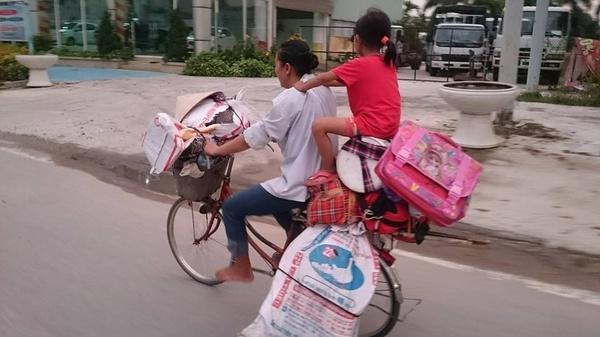 Người mẹ chân đất đạp xe chở con đi thu mua ve chai giữa trưa nắng.