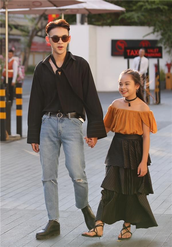 Dương Minh Tuấn và cô em gái Sunny Dương xuất hiện đầy thu hút với trang phục được phối trên nền những tông màu trầm như: xanh denim, đen, vàng nâu. 3 chi tiết đáng chú ý trên trang phục chính là khăn choàng, vòng cổ chocker và chân váy theo cấu trúc phân tầng.