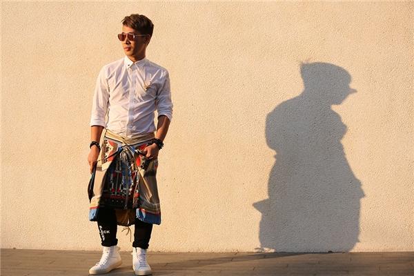 Áo sơ mi đi kèm quần jeans đen đơn giản, thanh lịch của Travis Nguyễn trở nên độc đáo hơn với chân váy họa tiết của Givenchy.