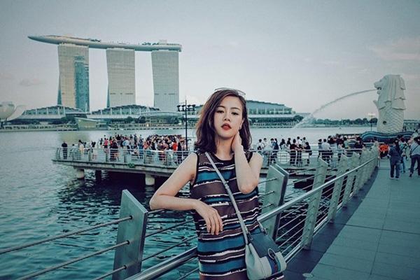 """Góc chụp thân quen với những ai từng ghé thăm Singapore với Marina Bay. Bức tượng đầu sư tử mình cá nhờ Phương Anh trở nên kỳ ảo và lung linh, với nét mặt """"chảnh"""" đặc trưng của cô, cùng tông màu xanh ma mị."""