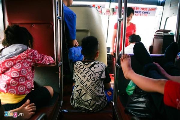 Bên trong một nhà xe chạy tuyến Giáp Bát - Sầm Sơn. Một em bé phải ngồi ở lối đi giữa hai hàng ghế vì hết chỗ.