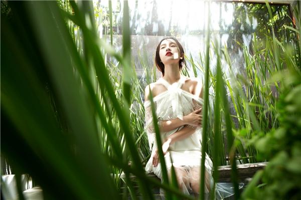 Jun Vũ hóa thân thành nàng tiên giáng trần giữa khung cảnh đầy sắc xanh tươi mát và những luồng ánh sáng mờ ảo. Bộ trang phục vẫn sử dụng phom suông quen thuộc nhưng lại tạo cảm giác mới mẻ với chất liệu ren bố trí ở phần ngực, vai và chân váy.