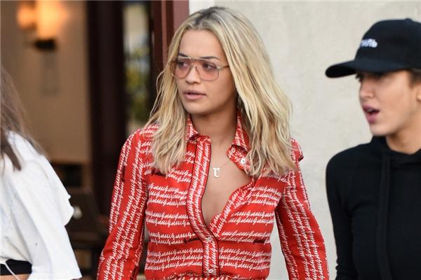 Trước Hồ Ngọc Hà, Rita Ora cũng từng diện mẫu thiết kế này nhưng với vẻ ngoài trẻ trung, cá tính, năng động hơn. Nữ ca sĩ danh tiếng chọn phối trang phục nghìn đô cùng bra màu vàng rực nổi bật bên trong. Phụ kiện đi kèm gồm kính trong suốt có màu hợp xu hướng và giày thể thao.