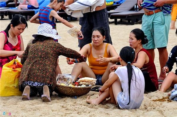 """Nơi đây vẫn còn nhiều người bán hàng rong. Họ mang đủ loại đồ ăn vặt đến tận nơi khách ngồi phục vụ. Chị Xuân (đến từ TP HCM) chia sẻ, """"cảm giác xuống bơi xong lên bờ cát được ăn đồ biển hoặc cái bánh, quả trứng cút thật là ngon""""."""