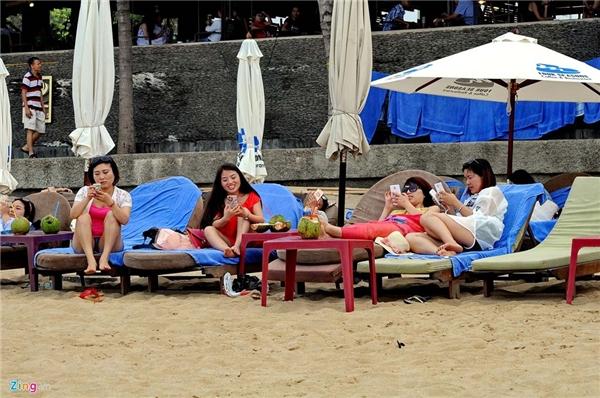 Một số cô gái đến từ quốc gia đông dân nhất thế giới không nhúng người xuống nước biển mà nằm ghế bố của khách sạn lướt Internet cùng nhau.
