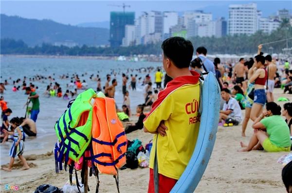 Nhân viên cứu hộ bãi biển chăm chú theo dõi du khách đề phòng bất trắc xảy ra. Anh còn tranh thủ kiếm thêm bằng công việc cho thuê áo phao, giá 20.000 đồng/chiếc.